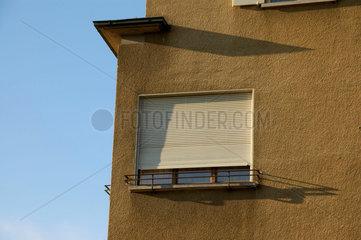 Fenster mit heruntergelassenen Rolladen am Morgen.