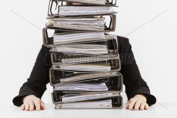 Woman is sinking behind mountains of folders  secretary  folders  work