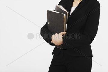 Frau mit Ordnern im Arm  Dokument  Kauffrau  Arbeitnehmerin  Geschaeftsfrau  Buerokratie  Ordnung  Angestellte  Business  Buero  Arbeit  Buerokratie  Akte  Ordner  Ablage  Termin  Anzug  Sekretaerin