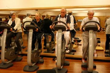 Senioren trainieren auf Fahrraedern