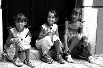 Drei freche Maedchen sitzen auf der Stiege