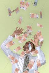 Geschaeftsmann; Geschaeftswelt; Business; Businessmann; Businesswelt; Regen; Geldregen; Geldsegen; eine Person; Mann; junger Mann; 18; 20; 25 Jahre; 20-25 Jahre; Portraet; frontal; Euro; Geld; Geldscheine; abstuetzen  Haende  Kopf  potential  Innenraum  schuld