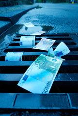 Gulli; Kanalisation; Euro; Geld; Strasse; Geldschein; Geldscheine; Finanzen; Gullideckel; liegen; Abfluss; 100; Ueberfluss; wegschmeissen; wertlos; Regenwasserabfluss; Regenwasser; abfliessen; Geldverlust; Verlust; Inflation; verlieren; Strasse; Regen; Banknote