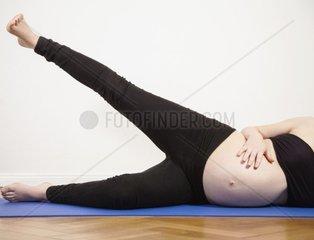 Junge schwangere Frau liegt auf der Seite  Meditation  Ruhe  Ausgleich  Ausgeglichen  Yoga  Bauch  Babybauch  werdende Mutter  Schwangerschaft  feminin  Namensfindung  Ausgleich  krankengymnastik
