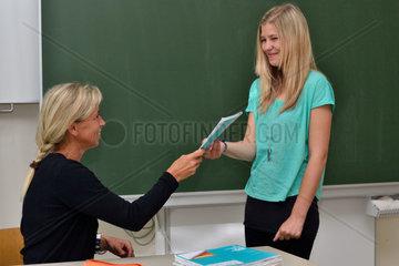 Mit Freude ueberreicht Lehrerin der Schuelerin ihr Heft