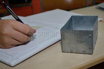 Facharbeiter zeichnet technischen Plan fuer Blechdosendeckel