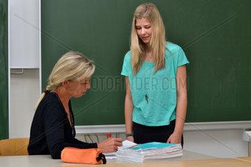 Lehrerin erklaert Schuelerin Ergebnisse der Hausuebung