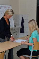 Lehrerin erklaert Schuelerin die Aufgabe im Heft