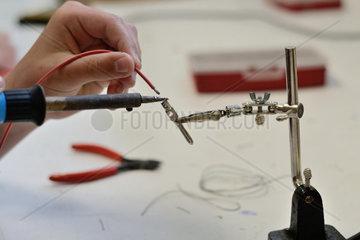Person beim Loeten von elektrischen Teilen