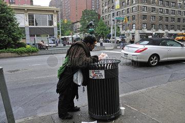 Ein Obdachloser durchsucht einen Muelleimer nach Verwertbarem  Manhattan  New York City  USA  Nordamerika  Amerika