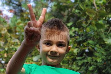 Kind zeigt Victory-Zeichen mit den Fingern