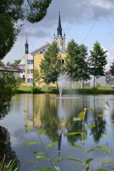 Kirchturm und anderes spiegelt sich in einer Teichanlage