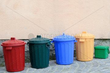 Biotonnen in verschiedenen Farben an einer Hausmauer