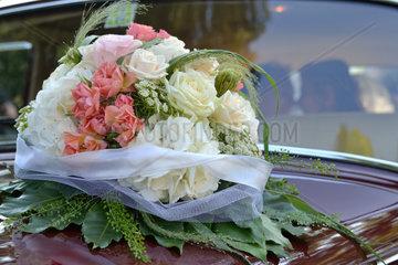 Bridal bouquet on wedding car  bride and groom in car
