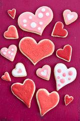 Bunte Herzen auf rotem Hintergrund aus Holz