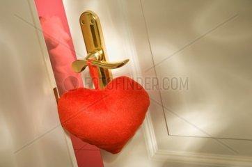 Ein rotes Herz haengt an einer Bordelltuer -