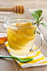 Tasse aus Glas mit heisser Zitrone und Honig