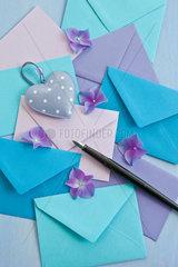 Bunte Briefumschlaege in Blautoenen mit Fueller als Hintergrund
