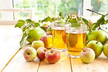 Klarer Apfelsaft in Glaesern mit frischen Aepfeln