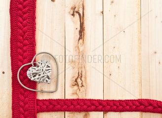 Hintergrund aus rustikalem Holz mit gestricktem Zopfmuster in Rot