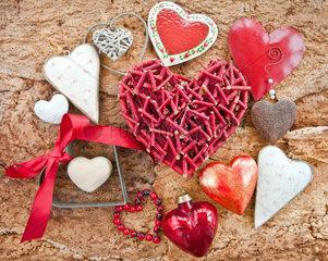 Verschiedene rote Herzen auf rustikalem Hintergrund aus Holz