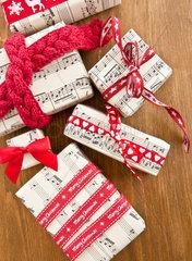 Kleine Geschenke mit roten Schleifen auf rustikalem Hintergrund aus Holz