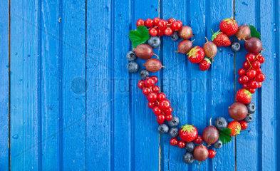 Blauer Hintergrund mit frischen Sommer Beeren in Herzform