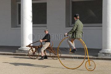 historrisch; Fahrrad; alt; zwei Personen; Vorfuehrung; Rad; Classic Bike; klassisch; Hochrad; Felgen; Speichen; Erfindung; Lenker; Laufmaschine; Draisine; Antrieb; gross; klein; hoch; vorne; hinten; Sattel; Antik; sitzen; fahren; Zweirad; Fortbewegung; Tran