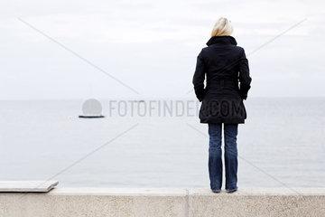 Frau die auf das Meer hinausschaut