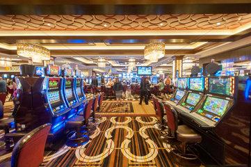 Interior of people in casino gambling on slot machines.