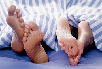 Bett; Paar; Decke; Fuesse; Zwei; Kuscheln; Querformat; Horizontal; liegen; lying; lies; liegend; liegendes; liegende; liegender; drinnen; indoor; innen; innenaufnahme; schlafzimmer; bedroom; im bett; in bed; fuesse; feet; fusssohle; sole; bettdecke; blanket