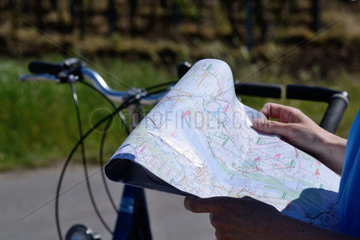Radfahrer sucht Orientierung auf einer Radwanderkarte