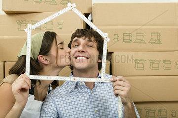 Junges Paar vor vielen Umzugskartons sieht durch Meterstab als Haus