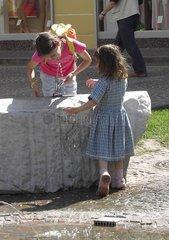 Kind trinkt Wasser am Brunnen