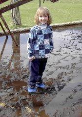Kind mit Gummistiefel im Dreck