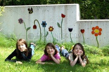 Drei Maedchen liegen im Gras mit Blumen