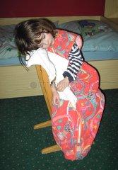 Kind schlaeft am Sessel