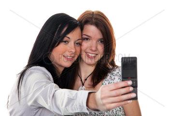 Zwei huebsche junge Freundinnen machen ein Foto mit dem Handy