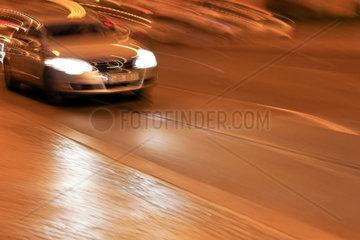Ein fahrendes Auto mit Licht am Abend auf einer Strasse