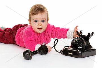Liegendes kleines Kind spielt mit einem alten Telefon