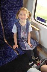 Froehliches Maedchen sitzt im Zug