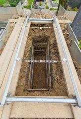 Leeres und offenes Grab auf einem Friedhof