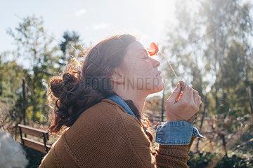 Junge Frau mit einer Klatschmohnbluete
