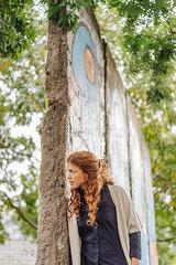 Junge Frau an einem Teilstueck der alten Berliner Mauer