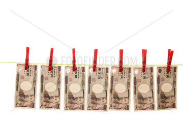 Symbol fuer Geldwaesche mit japanischen YEN auf Waescheleine