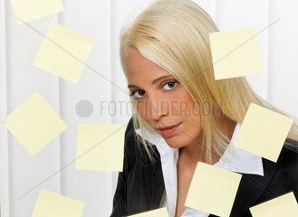 Gestresste junge Frau mit vielfaeltigen Aufgaben Merkzetteln