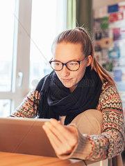 Junge Frau mit Brille schaut auf Tablet