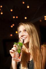 Junge Frau trinkt durch einen Strohalm Limonade