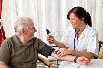 Eine junge ssrztin misst Patientin den Blutdruck