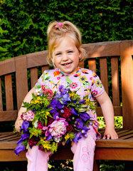 Kleines Kind mit Blumenstrauss Geschenk fuer Muttertag